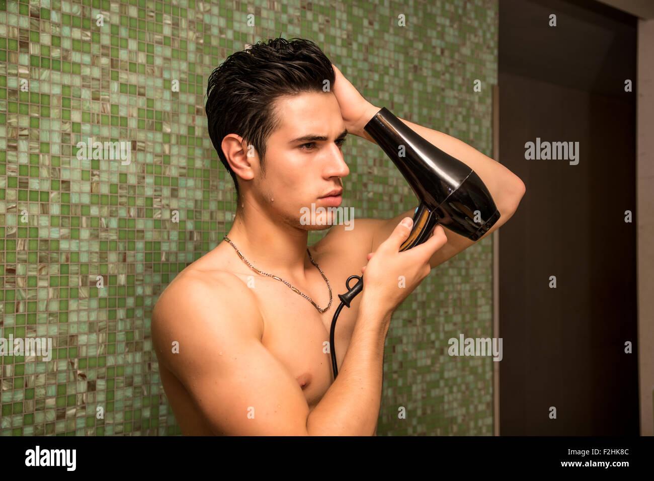 Jeune homme torse nu les cheveux de séchage avec un sèche-cheveux, miroir à à la maison Photo Stock