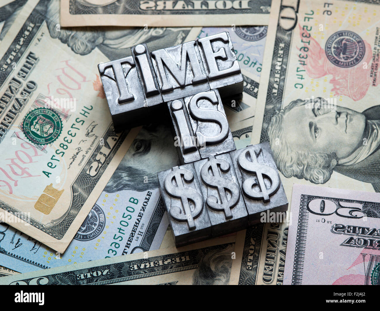 Time is money concept faits de type typographique métallique sur tas de dollars US Photo Stock