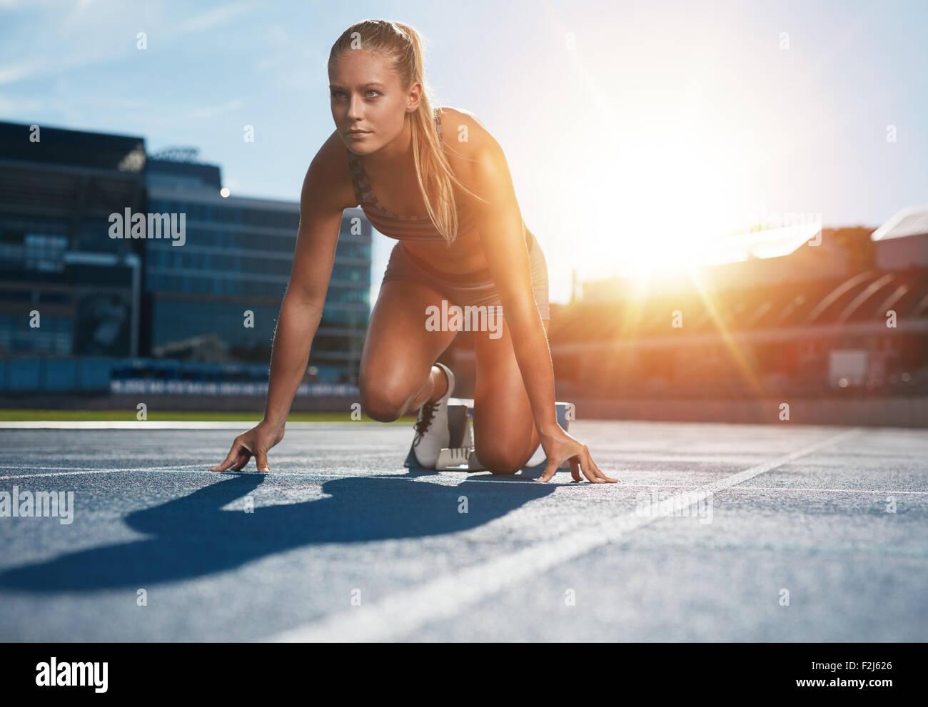Mettre en place et en confiance femme en position de départ prêt pour la course. Athlète féminin sur le point de commencer un sprint à la route. Sunl lumineux Banque D'Images