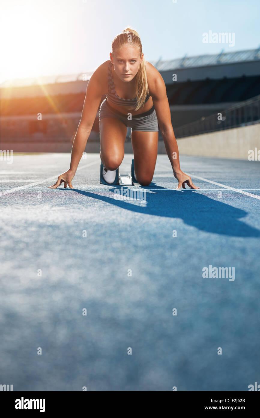 Jeune femme sprinter dans la position de démarrage sur une piste de course à un stade à la recherche jusqu'à l'appareil photo avec détermination. Runner Banque D'Images