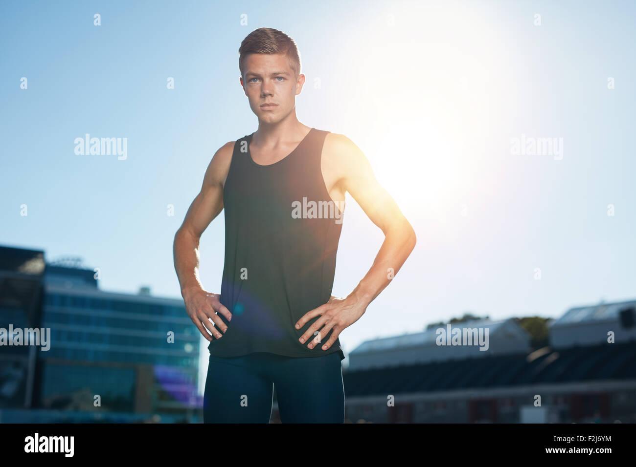 Tourné en plein air de jeune homme sur la préparation du stade pour une course. Athlète masculin Photo Stock