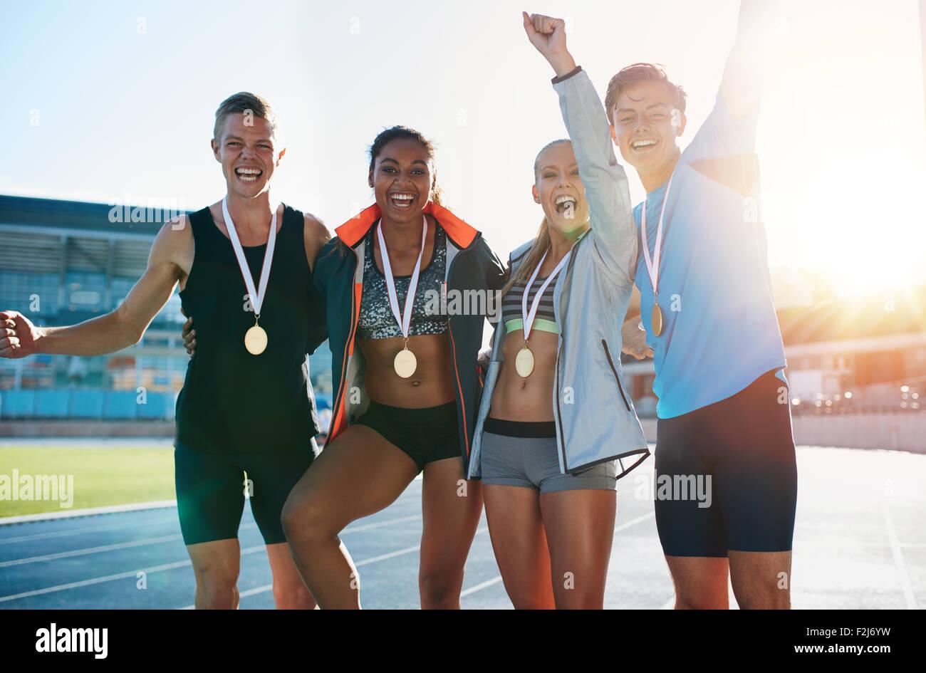 Portrait de jeunes athlètes extatique avec des médailles. Groupe de coureurs se tenant ensemble smiling Photo Stock