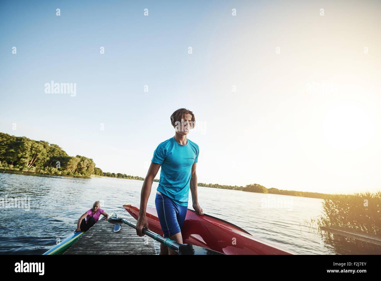 Jeune homme portant un kayak après être sorti de l'eau Banque D'Images
