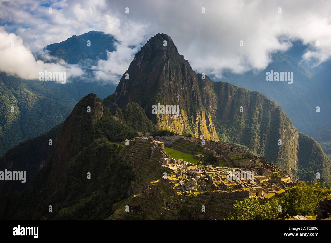 Machu Picchu illuminée par les premiers rayons du soleil qui sort de l'ouverture des nuages. La ville de Photo Stock