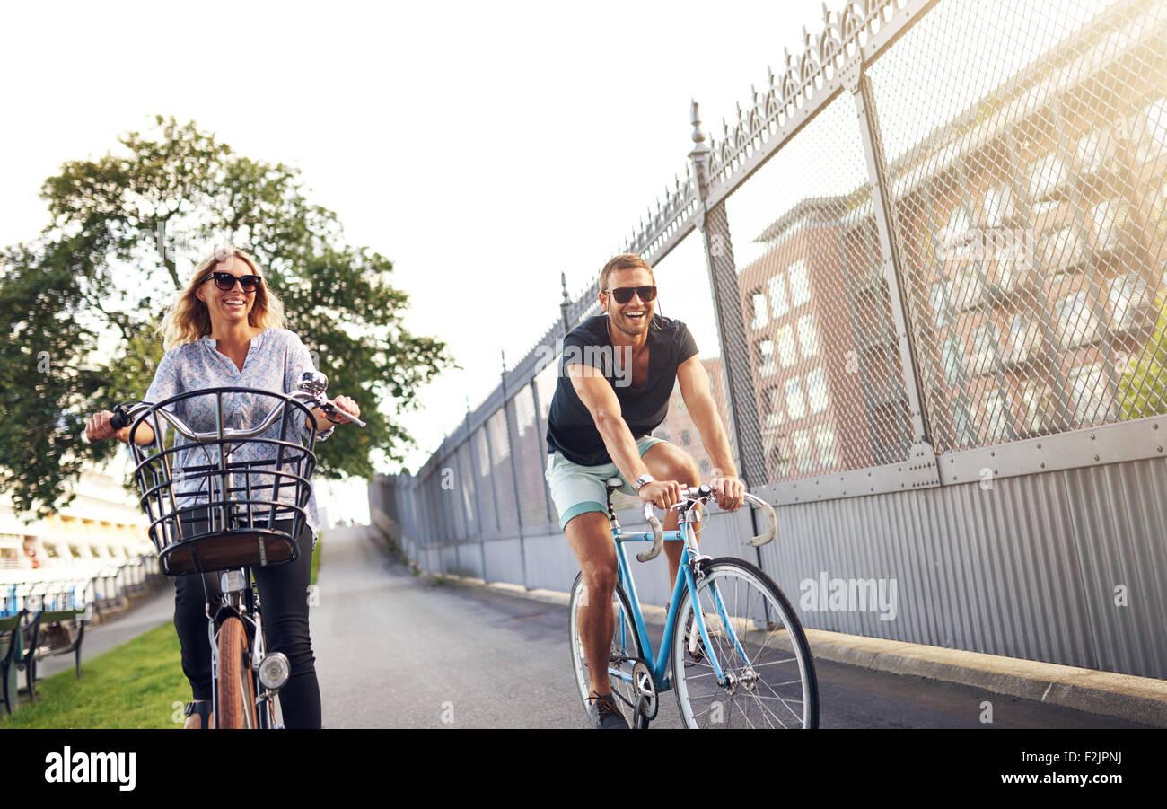 Jeune couple à vélo dans un parc urbain comme ils jouissent d'une saine vie de plein air dans l'air frais et de soleil de l'été Banque D'Images