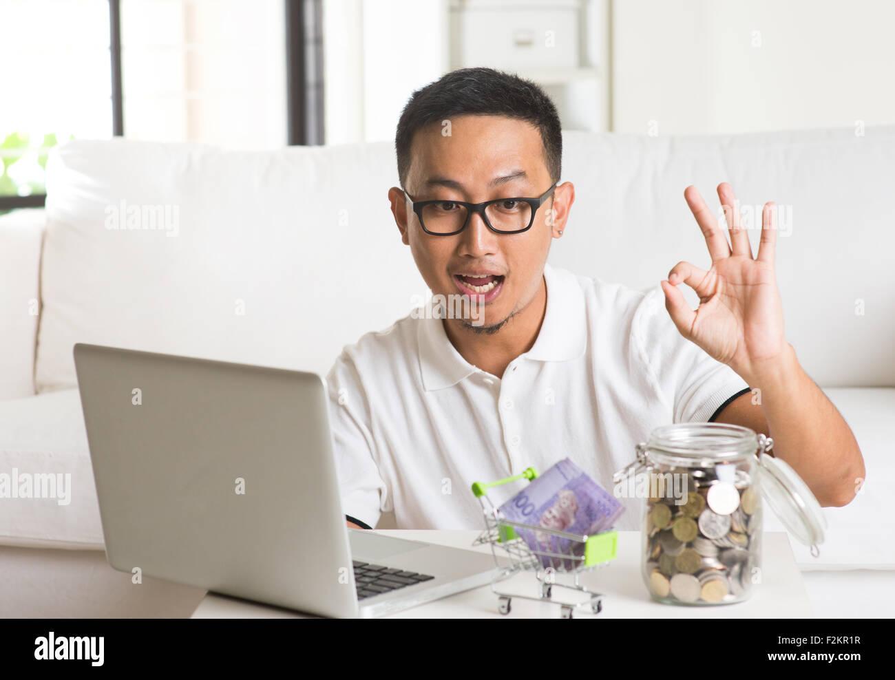 asiatique à l'aide d'internet et informatique à compter des pièces à