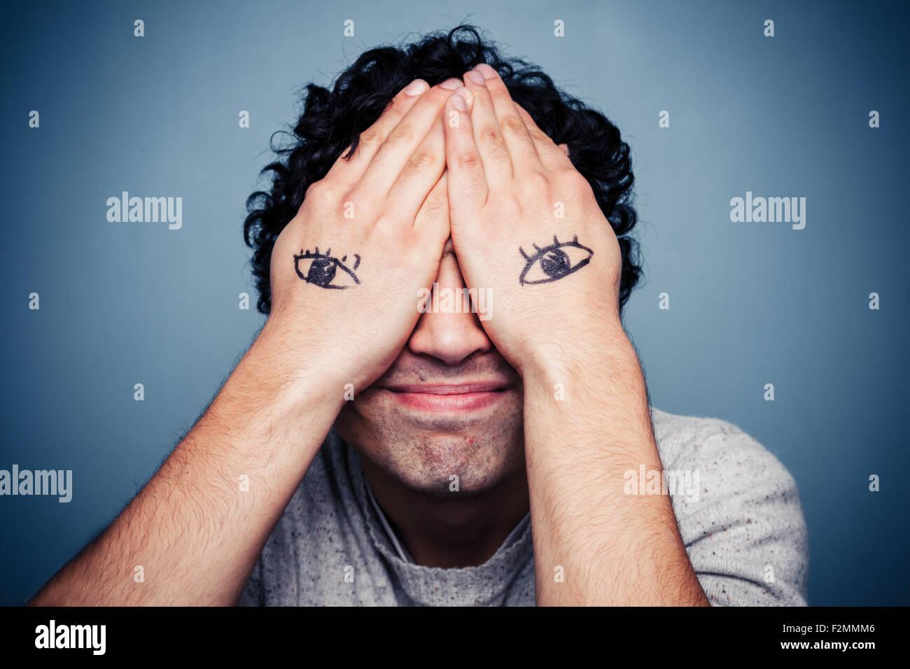 Jeune homme avec les yeux peints sur les mains Photo Stock