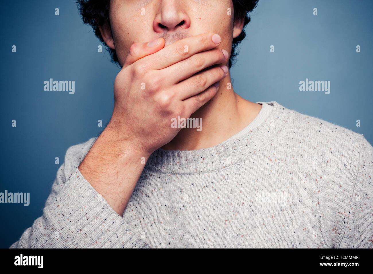Jeune homme couvrant la bouche sous le choc Photo Stock