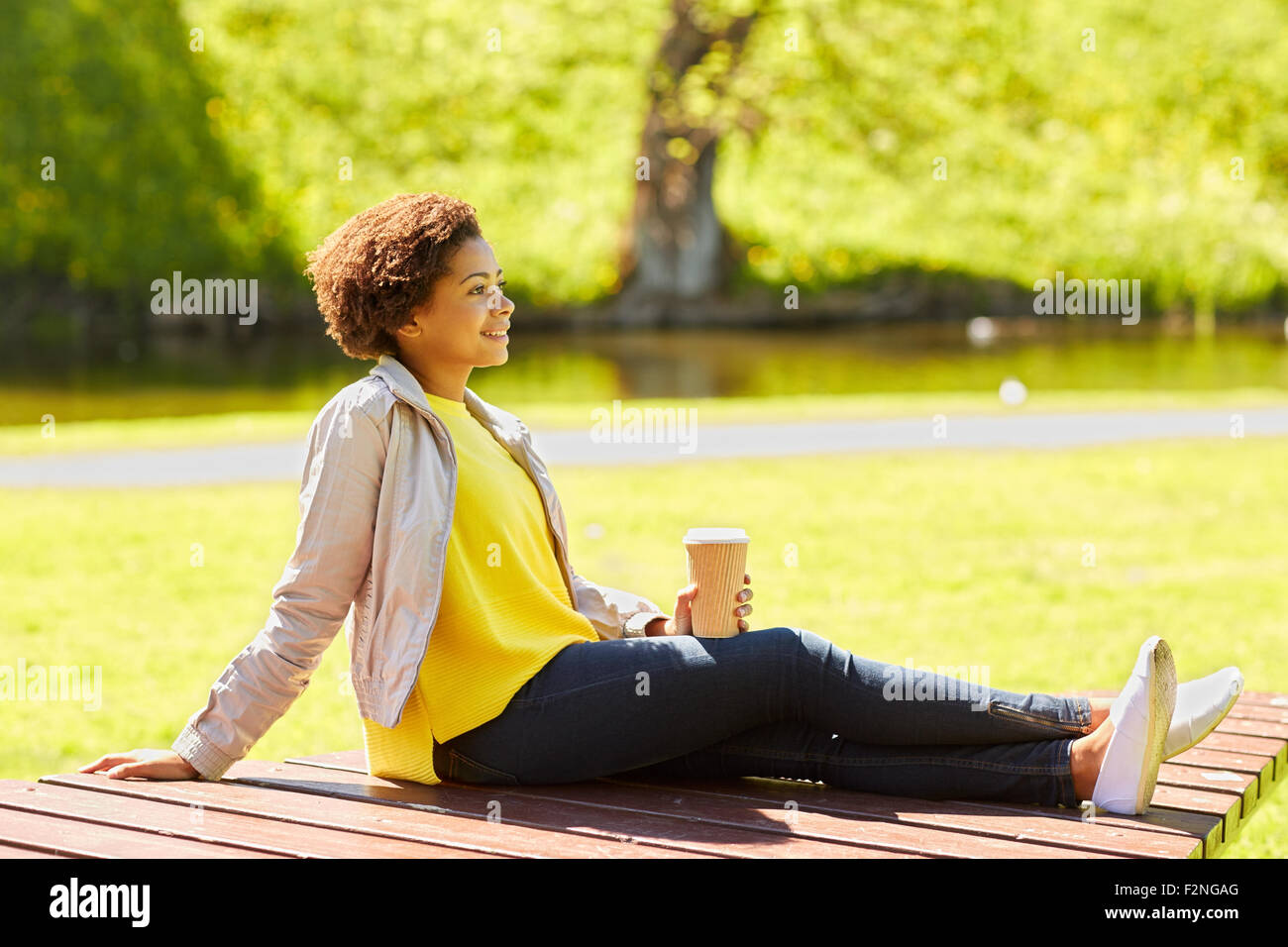 Happy african femme boit du café au parc d'été Banque D'Images