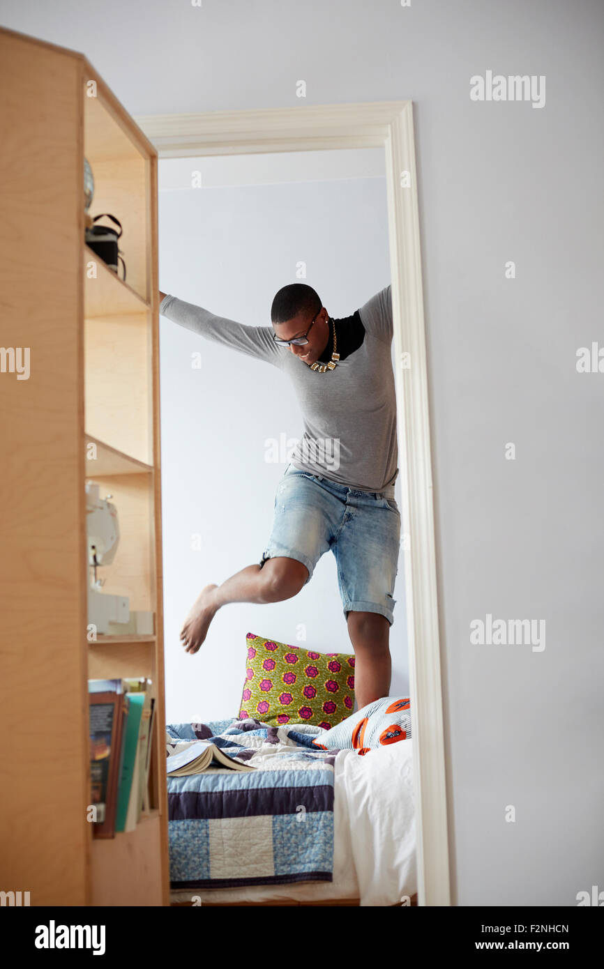Mixed Race woman jumping on bed Banque D'Images