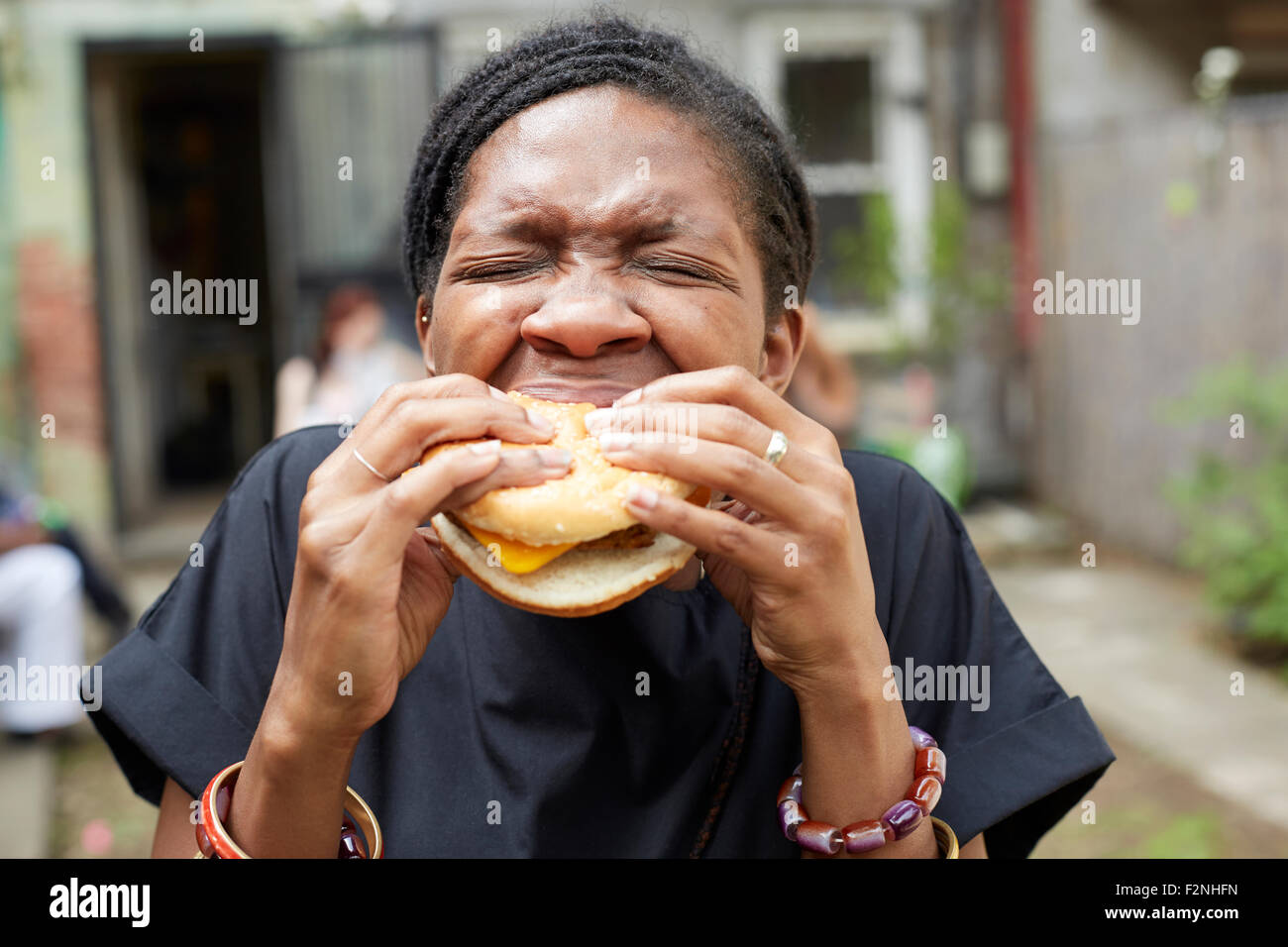 African American Woman eating at backyard barbecue Banque D'Images