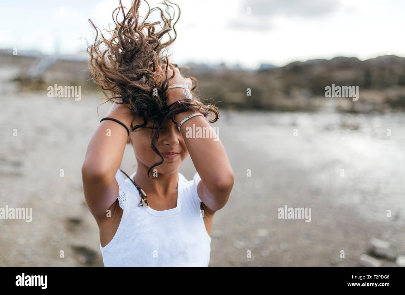 L'Espagne, Gijon, petite fille sur la plage tenant son souffle d'un sèche Photo Stock