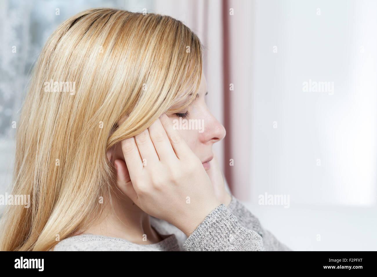 Femme tenant les mains sur la tête à cause de maux de tête Banque D'Images