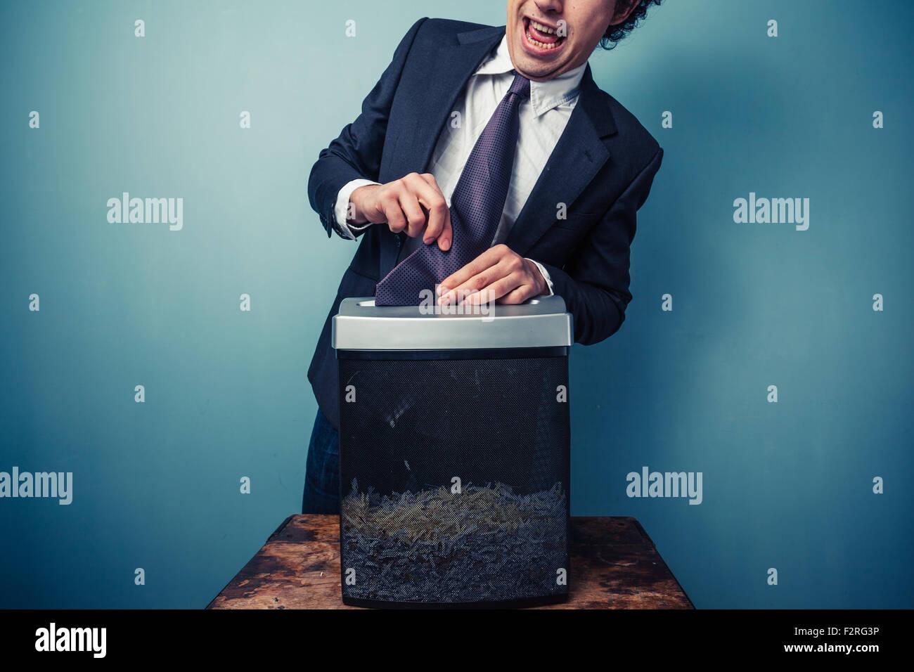 Homme maladroit avec sa cravate coincée dans une déchiqueteuse Photo Stock