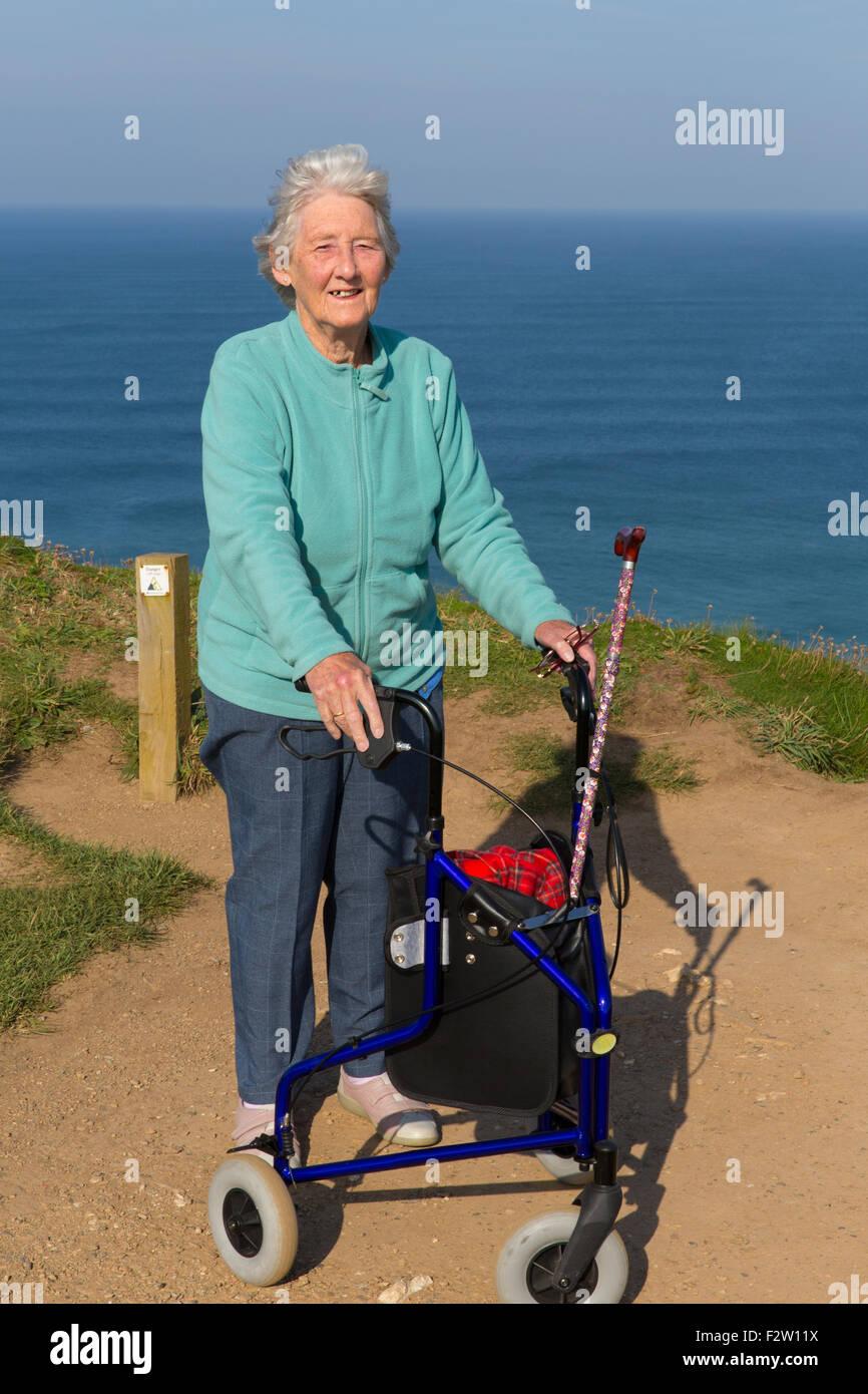 Jeune femme active pensionné avec trois roues chariot aide à la mobilité par coast Photo Stock