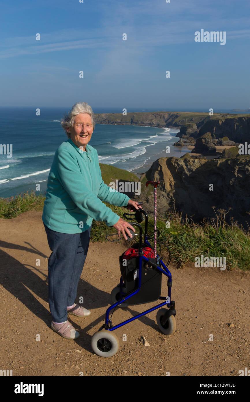 Vieille dame actif pensionné avec trois roues chariot aide à la mobilité par la belle scène Photo Stock