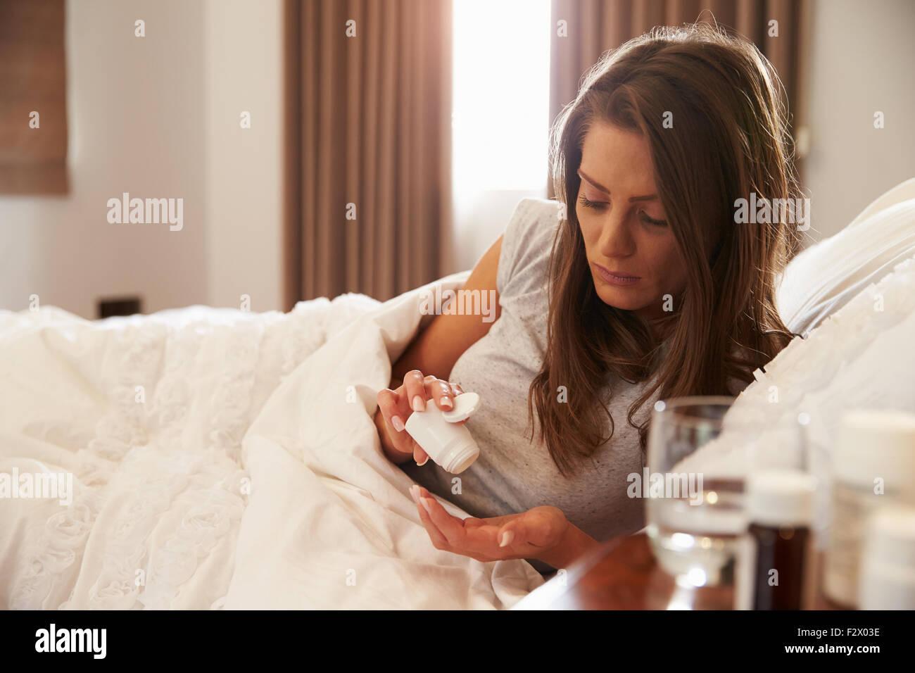 Femme de prendre des médicaments à partir de conteneurs sur Table de chevet Photo Stock