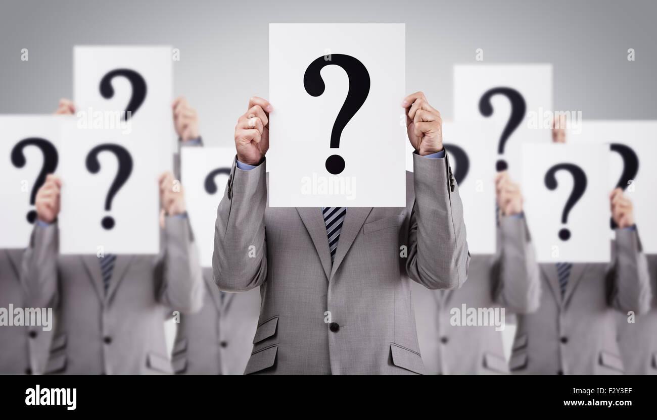 Des collègues d'affaires holding point d'interrogation dans leurs visages Photo Stock