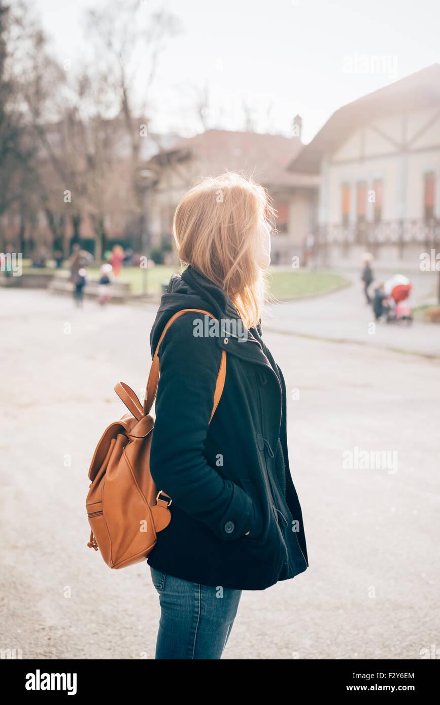 profil de de sportive belle figure à La sac dos la vêtu femme manteau et sur de blonde la gauche d'une ville hippie noir du jeune donnant genou ItqaIWCfxw