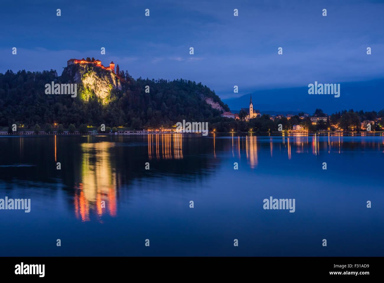Château de Bled illuminé au lac de Bled en Slovénie dans la nuit compte sur surface de l'eau Photo Stock