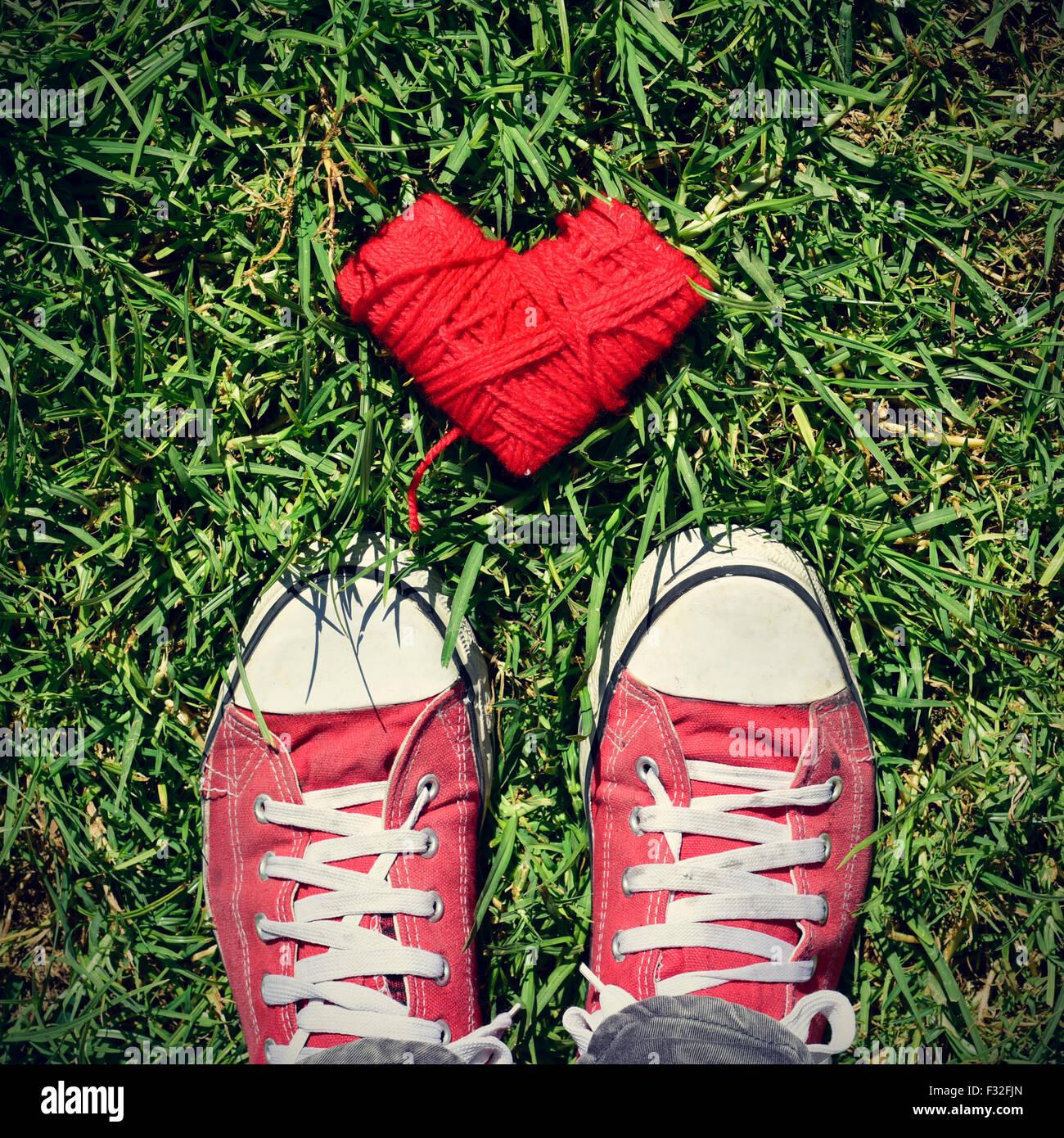 Une bobine en forme de cœur rouge de la corde et les pieds d'un homme portant des chaussures de marche sur l'herbe, Photo Stock