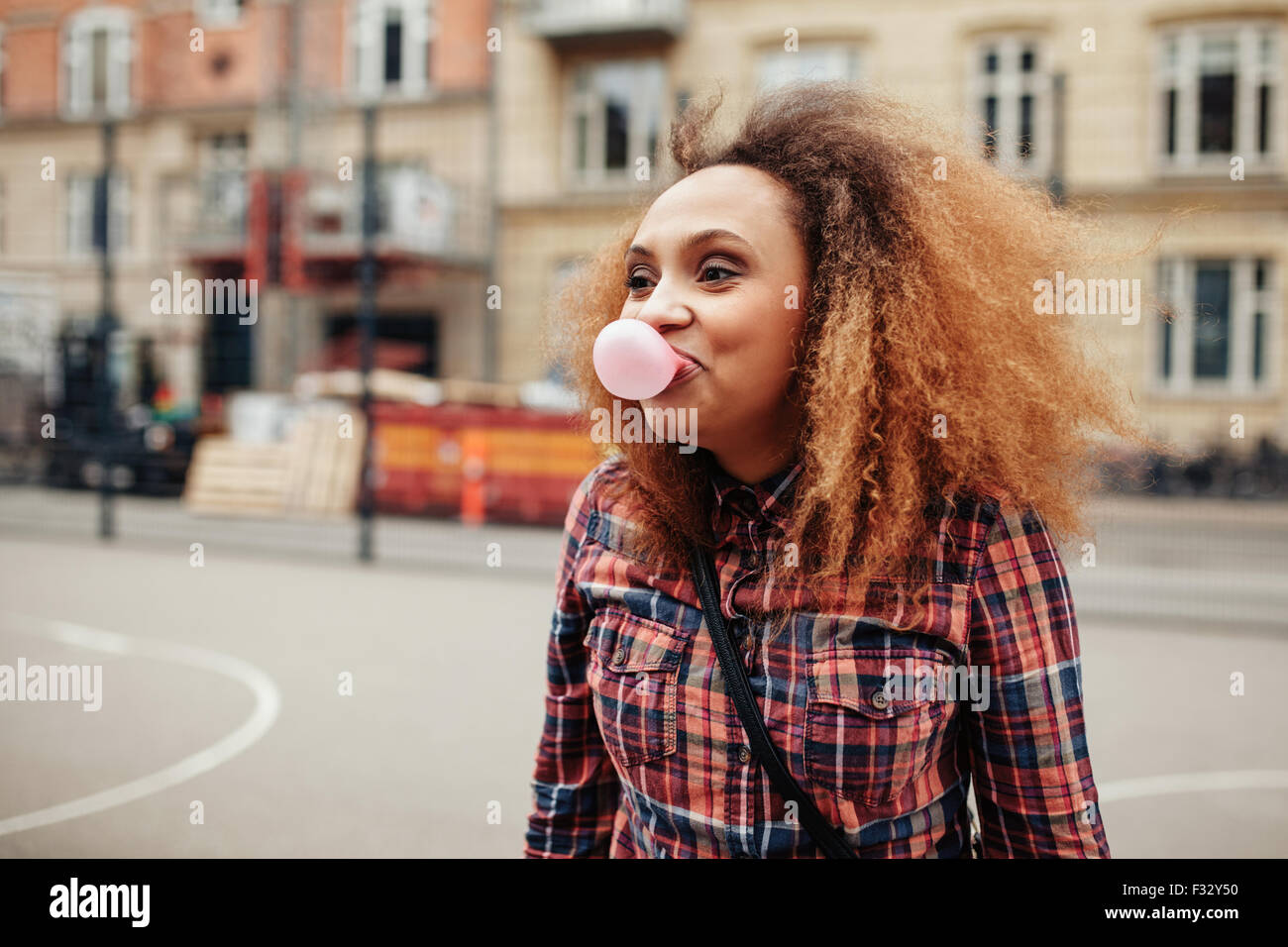 Jeune femme africaine souffle une bulle avec son chewing-gum. Casual young woman on city street s'amusant. Photo Stock