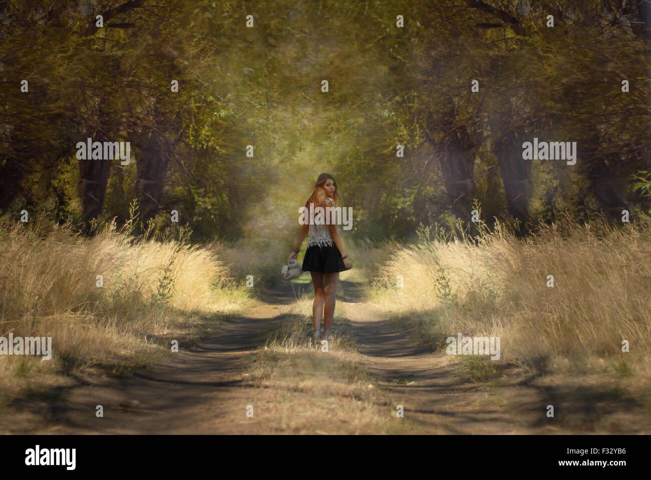 Grande fille à trouhgt la forêt à l'arrière Banque D'Images