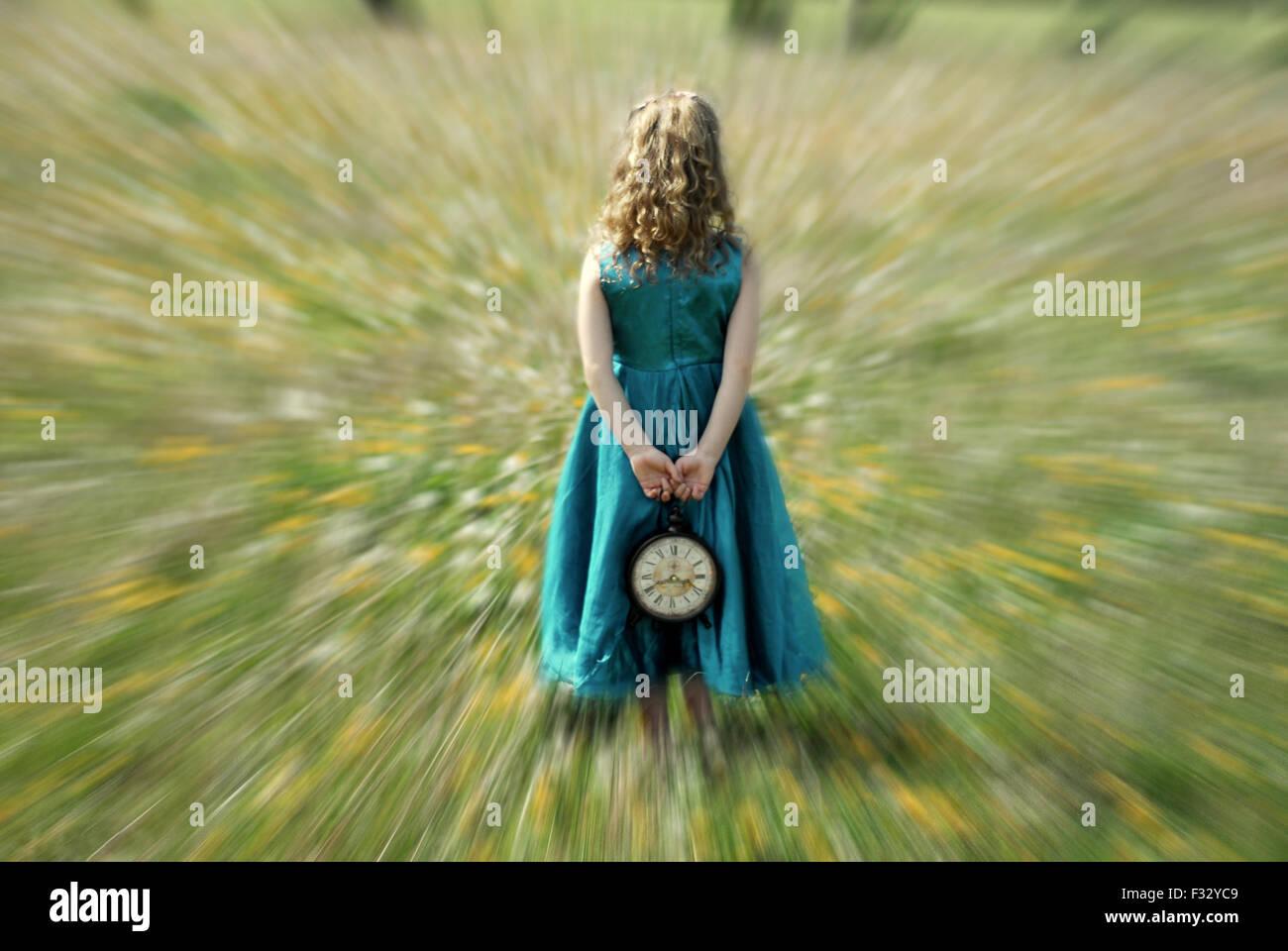 Effet de zoom petite fille avec réveil dans ses mains blue dress wonderland Photo Stock