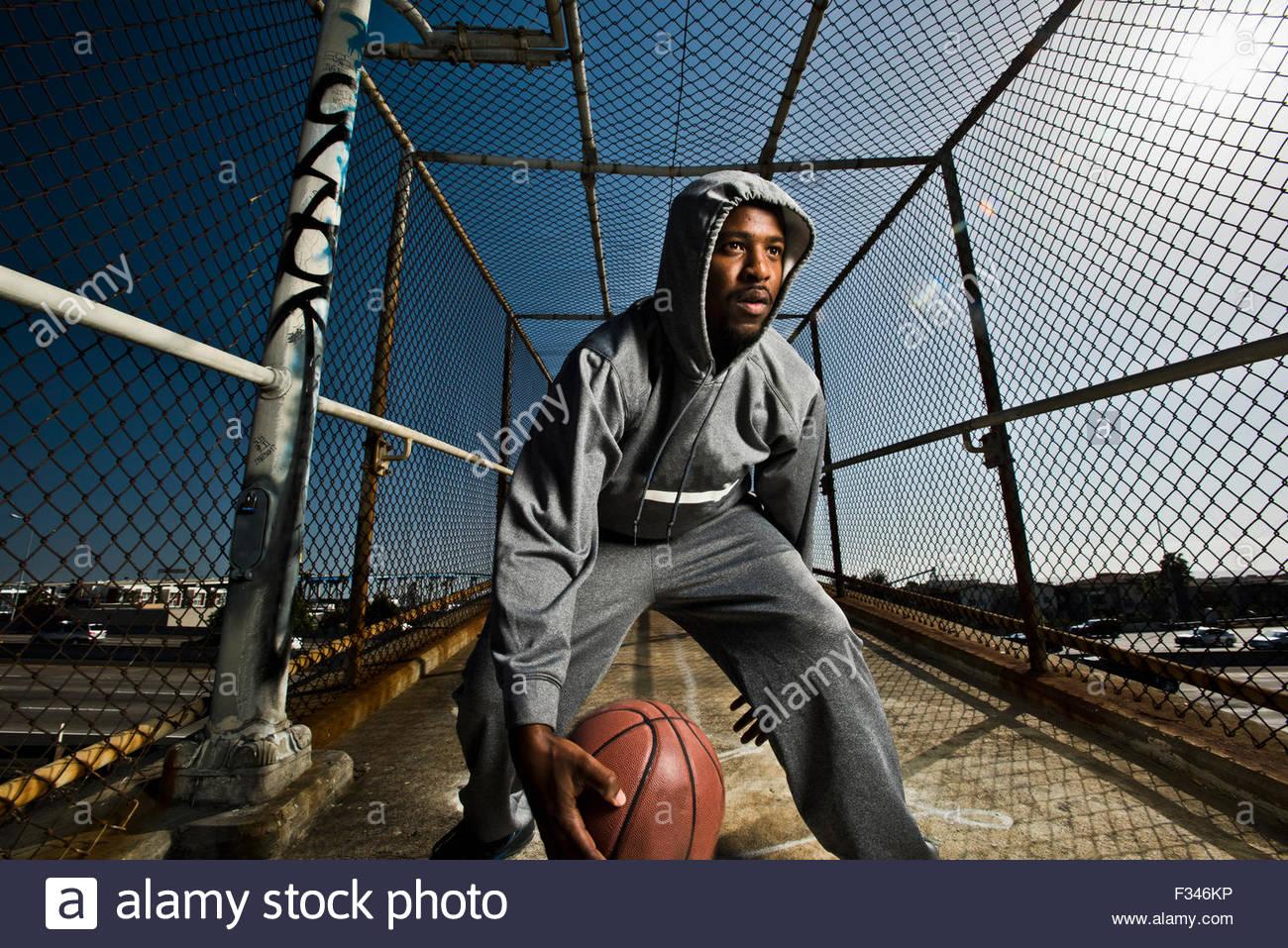 Un jeune homme de jouer avec un ballon de basket-ball. Photo Stock