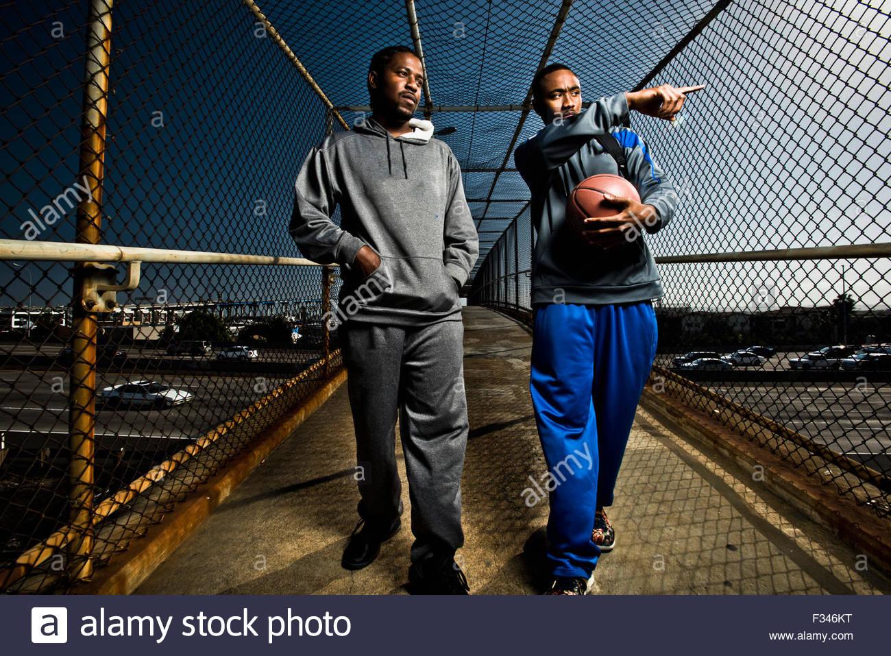 Deux jeunes hommes se promener avec un terrain de basket-ball. Photo Stock