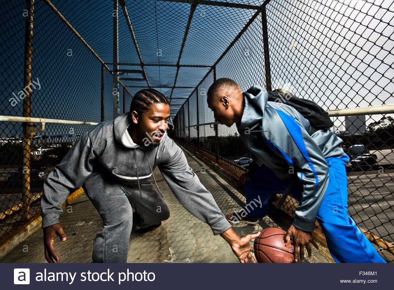Deux jeunes hommes marchant sur une passerelle de jouer avec un ballon de basket-ball. Photo Stock