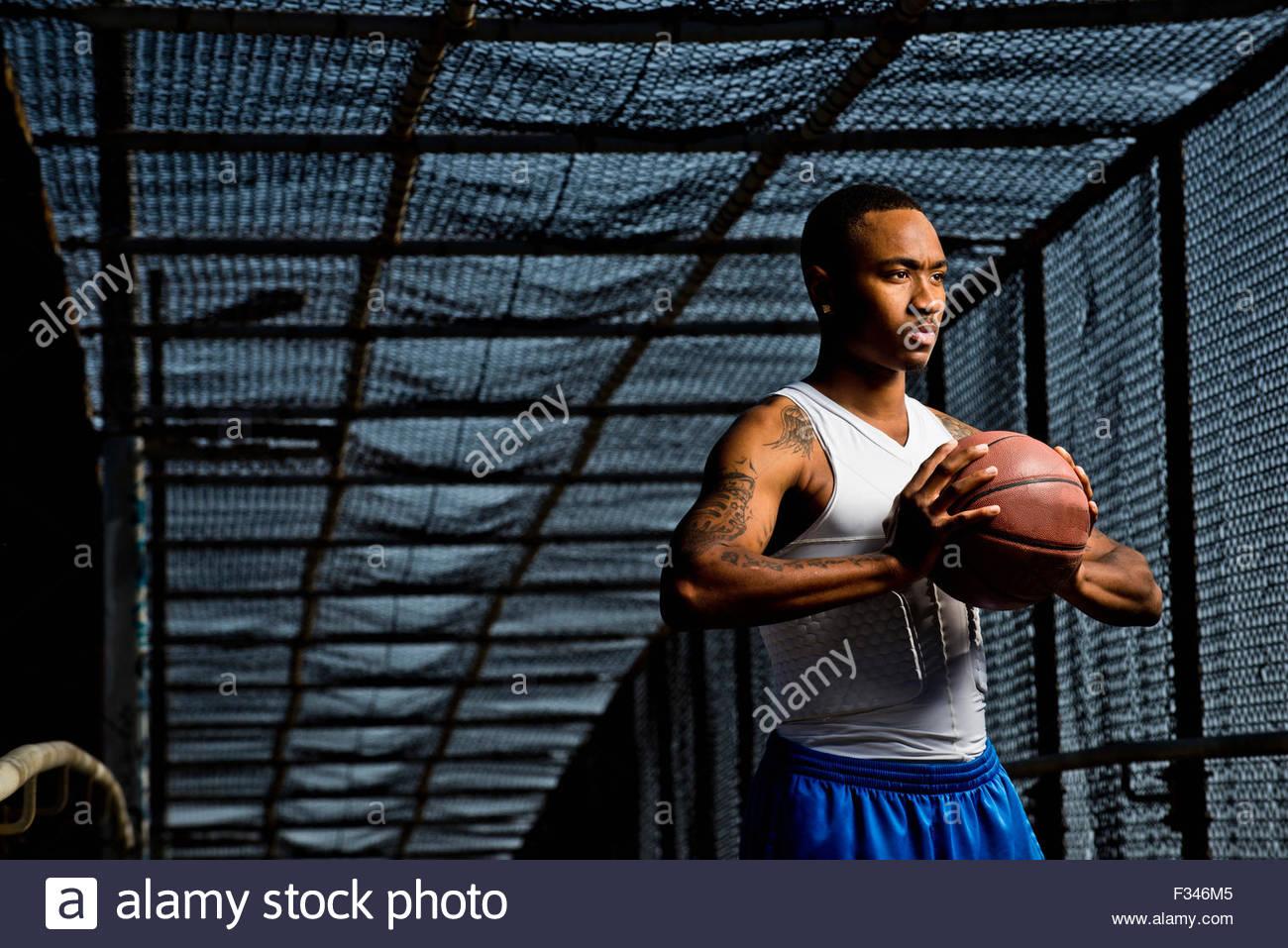 Un jeune homme pose avec un terrain de basket-ball. Photo Stock