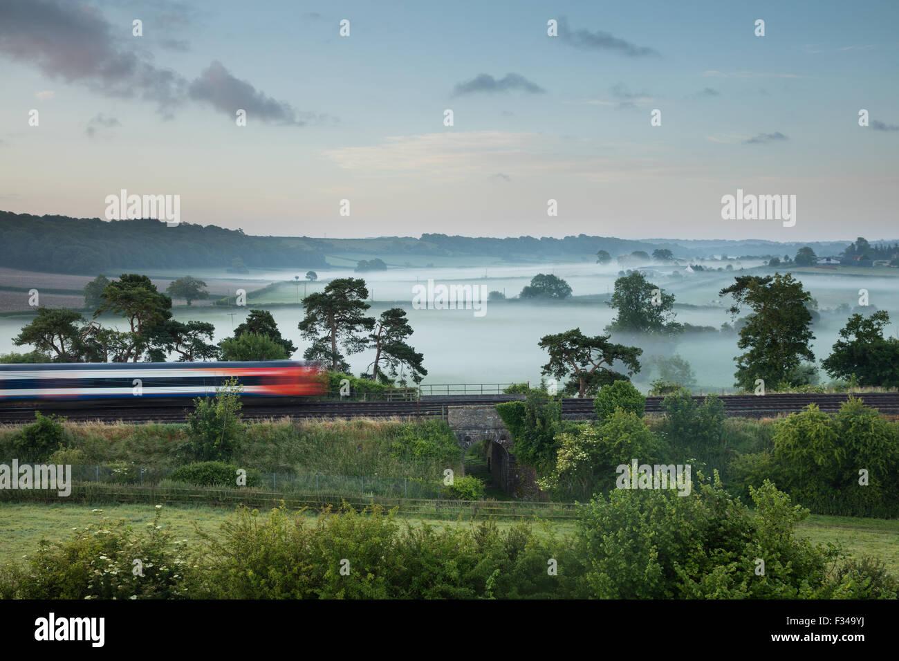 La London Waterloo à Exeter train Milborne Wick sur un matin d'été brumeux, Somerset, England, Photo Stock