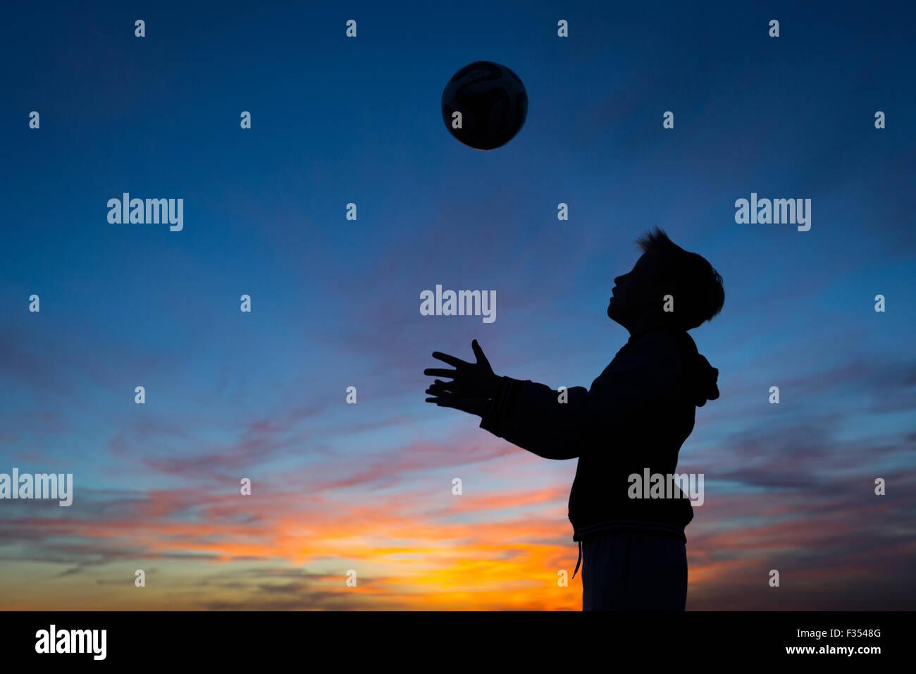Silhouette d'un garçon jouant à l'extérieur au crépuscule Photo Stock