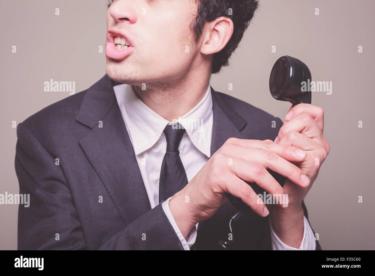 Jeune homme d'affaires est le faire taire quelqu'un afin d'entendre le téléphone Photo Stock