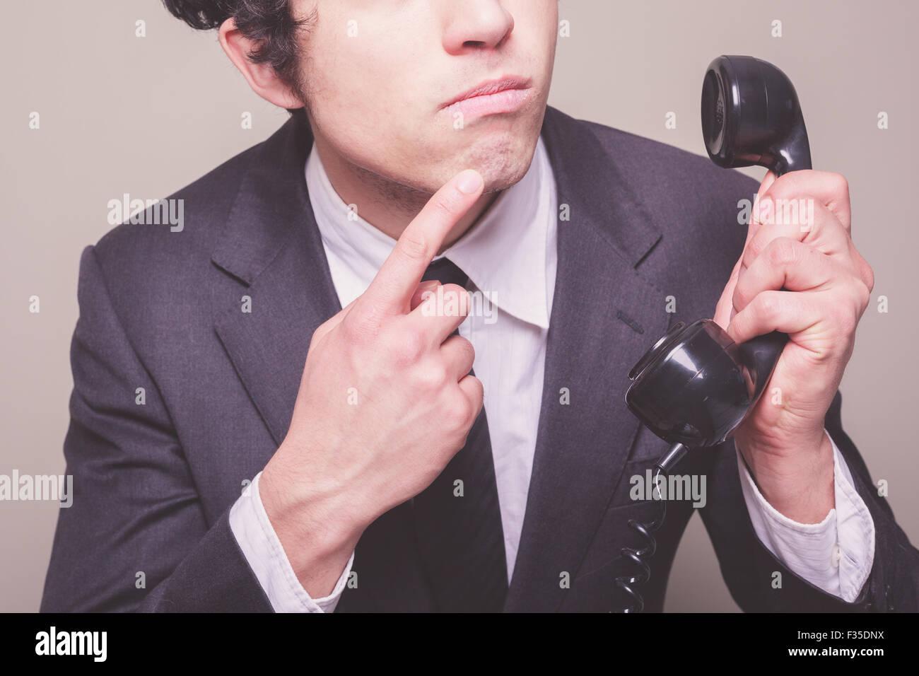 Jeune homme d'affaires est au téléphone et pense à ce qu'il faut dire Banque D'Images