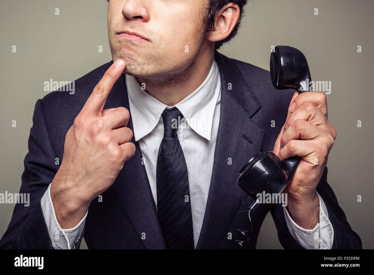 Jeune homme d'affaires est au téléphone et pense à ce qu'il faut dire Photo Stock