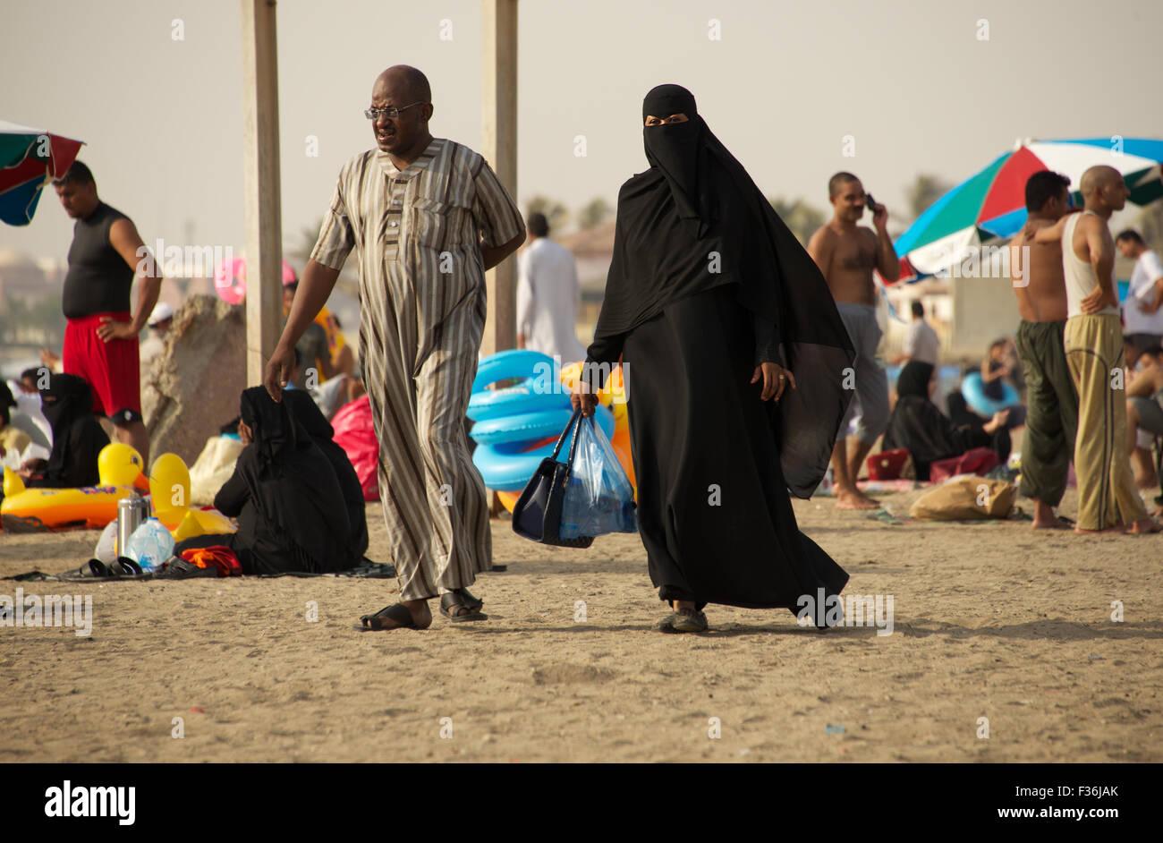 Couple strolling musulmane sur plage de la mer Rouge, à Djeddah, Arabie Saoudite Photo Stock