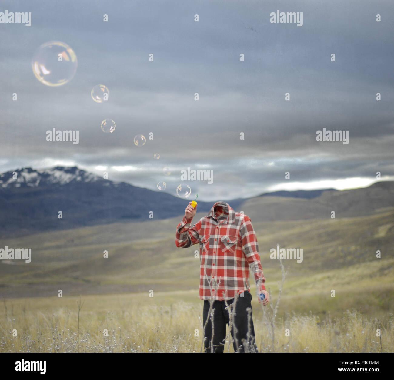 L'homme sans tête blowing bubbles montagne ciel orageux Photo Stock