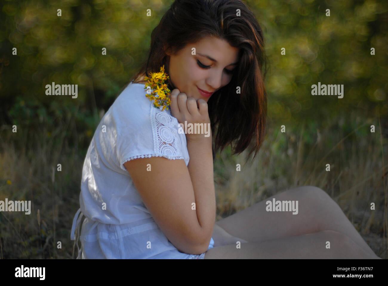 Belle fille à la recherche vers le bas avec des fleurs jaunes dans ses mains dans une robe blanche Banque D'Images