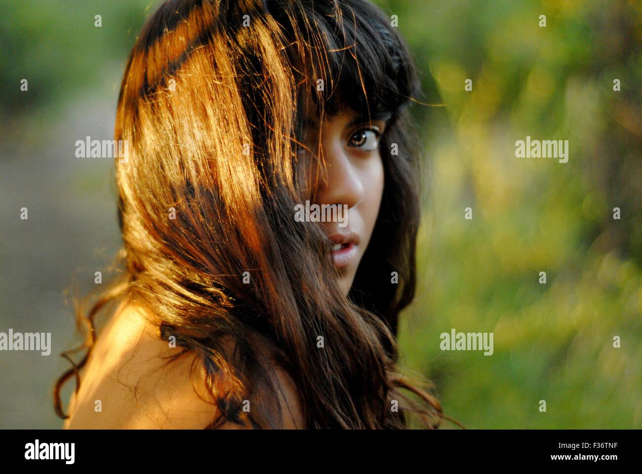 Fille sauvage avec des yeux verts au milieu de la jungle très regard profond reflet Photo Stock