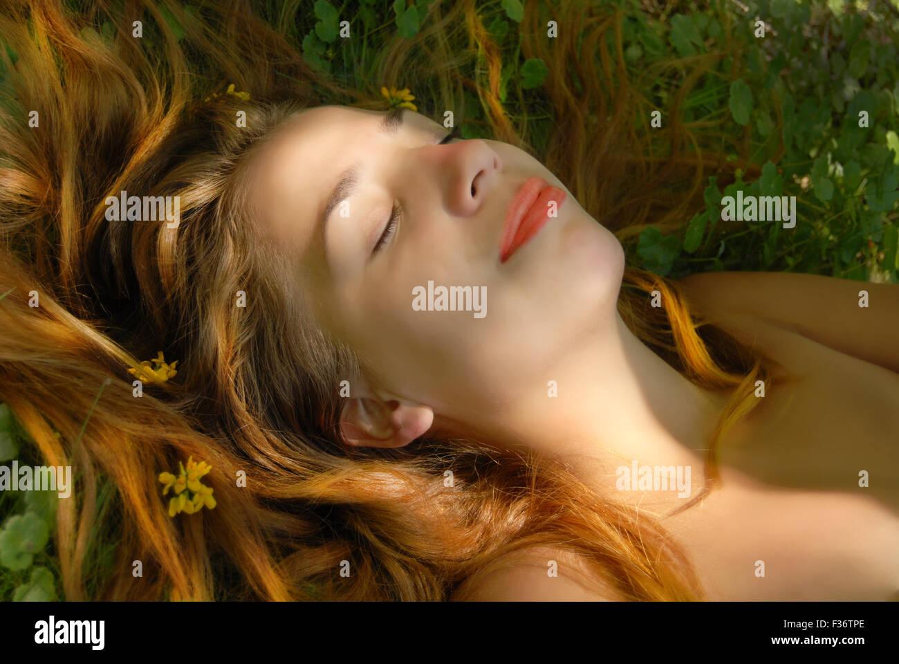 Fille blonde portant dans l'herbe avec des fleurs lèvres rouge peau parfaite Photo Stock