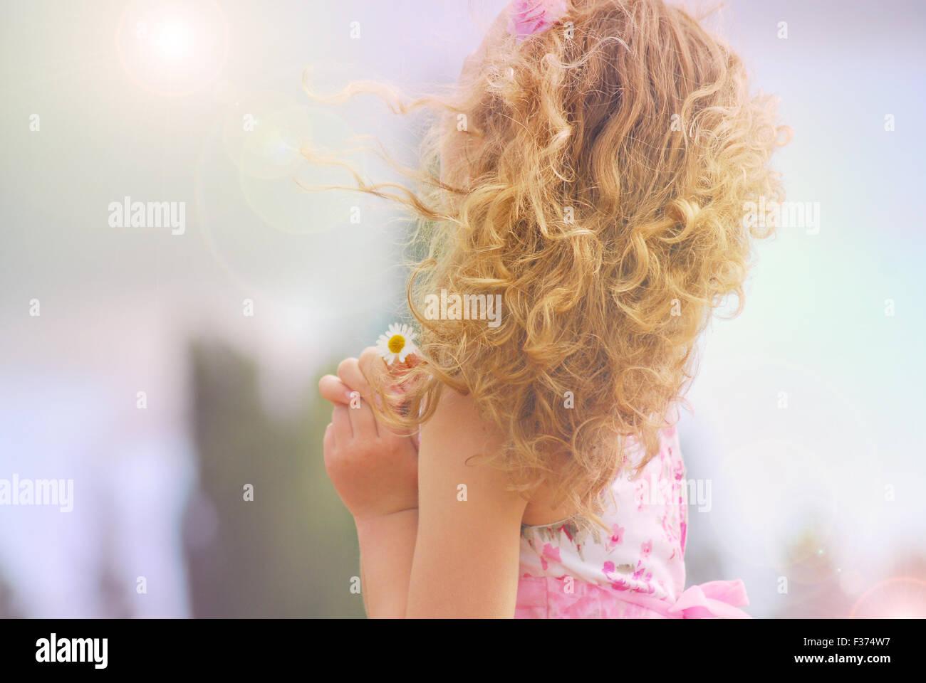 Jolie petite fille avec une fleur dans ses mains à la recherche le soleil et le ciel Photo Stock
