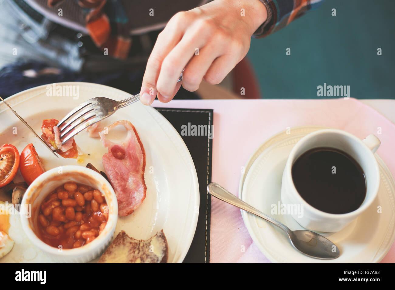 Gros plan sur les mains d'une jeune femme comme elle est de prendre le petit déjeuner Photo Stock