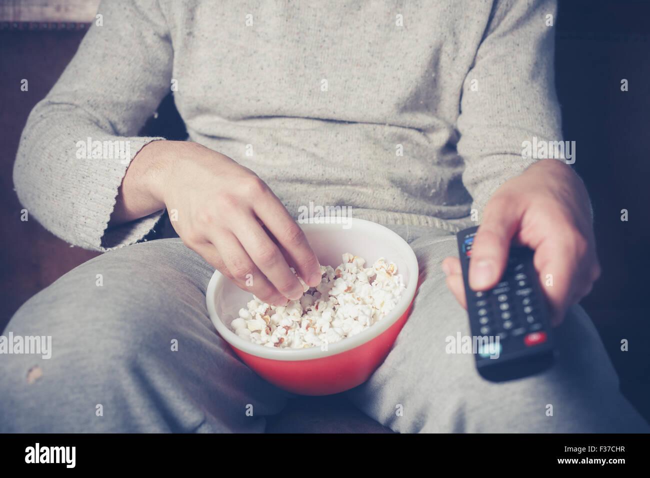Jeune homme est assis sur un canapé et manger du popcorn en regardant la télévision Photo Stock