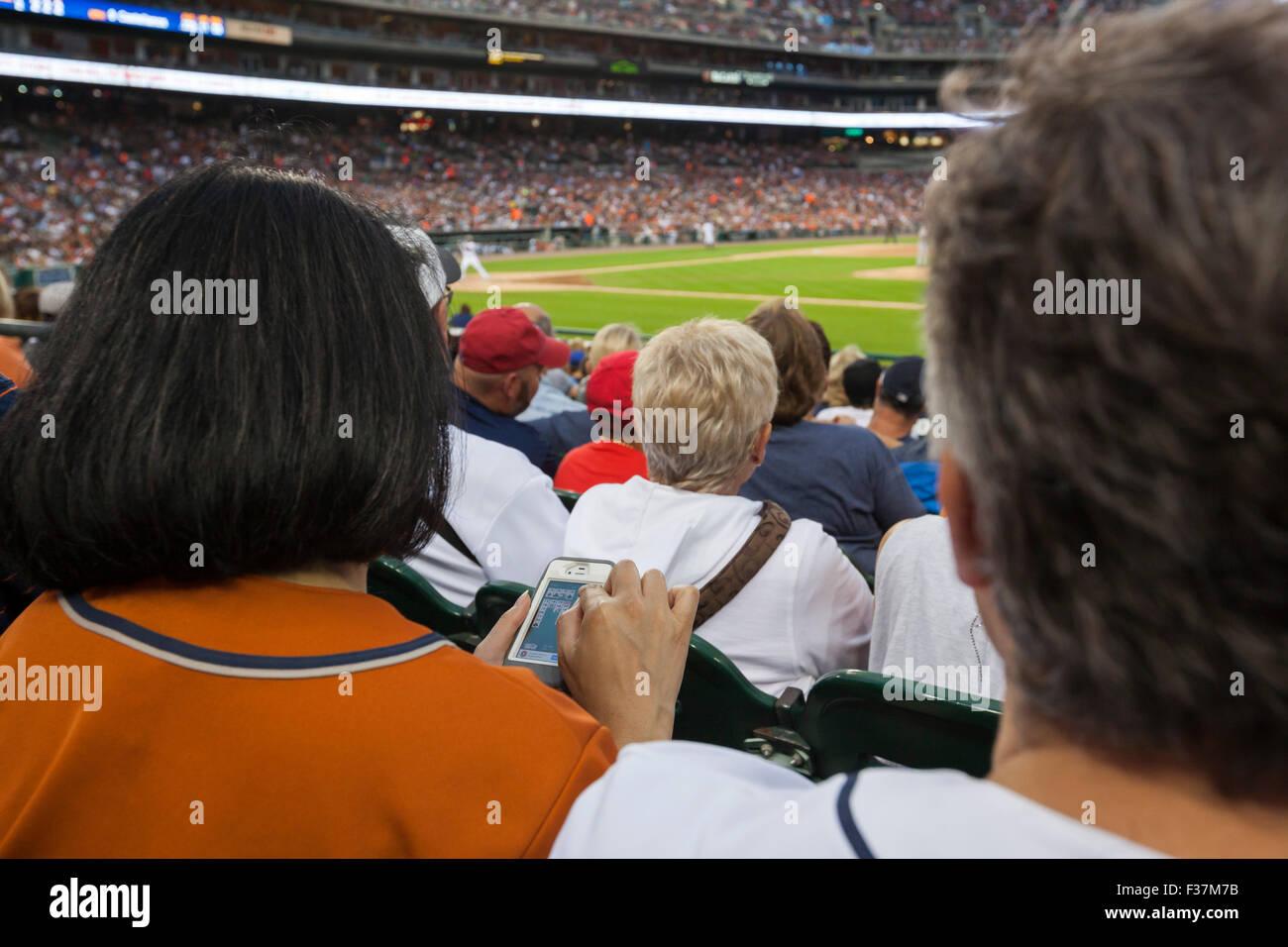 Detroit, Michigan - Une femme joue solitaire sur son téléphone au Comerica Park lors d'un match de Photo Stock