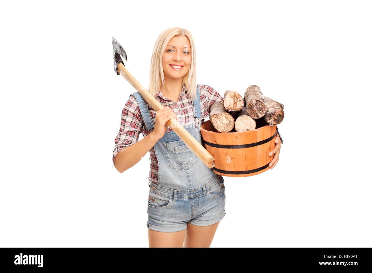 Jeune femme blonde en chemise à carreaux tenant un seau plein de billes et de transporter une hache à l'épaule Banque D'Images