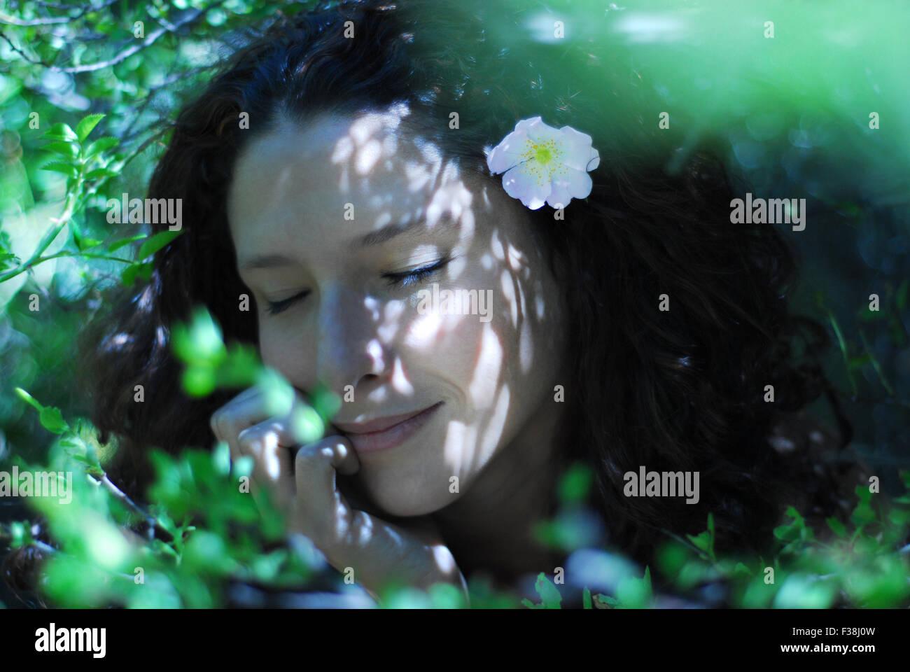 Cute girl entre beaucoup de feuilles vertes avec petite fleur rose tendre dans ses cheveux bouclés Photo Stock