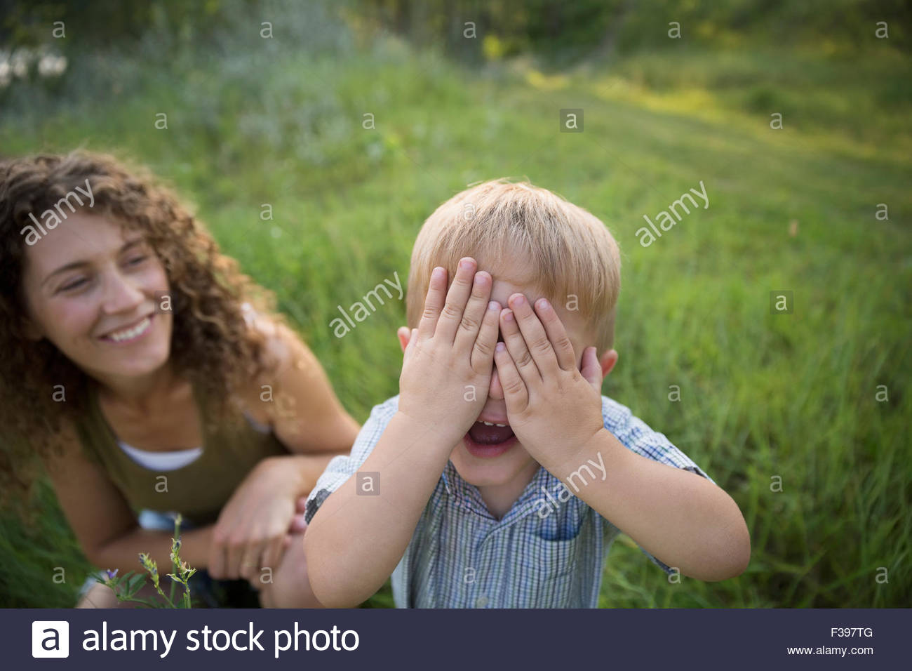 Portrait mère regardant fils jouer peek-a-boo Photo Stock
