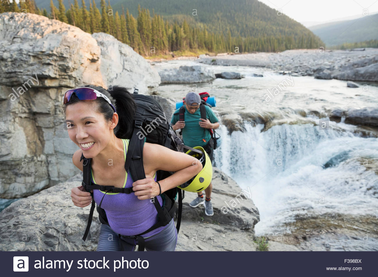 Female hiker with backpack près de craggy waterfall Banque D'Images